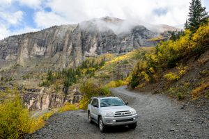 Telluride, Colorado, USA - October 05, 2015: on a cloudy and foggy autumn day, a four-wheel-drive SUV is exploring in colorful autumn mountains on the winding Black Bear Pass trail, near Telluride, Colorado, USA.